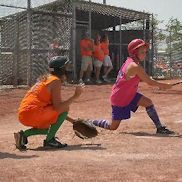 GIrl swinging at the plate with a catcher behind her